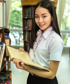 teenage girl holding book in library