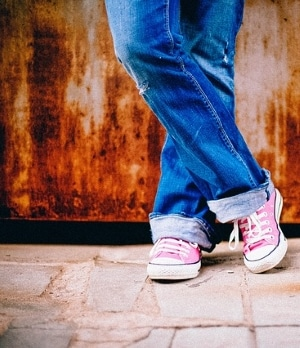 teen in jeans and sneakers against wall in city