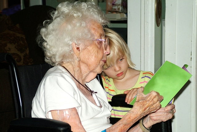 elderly woman in wheelchair reading with child