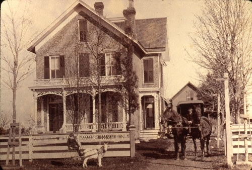 horse-drawn carriage and goat pulling a cart with a boy, in front of brick house