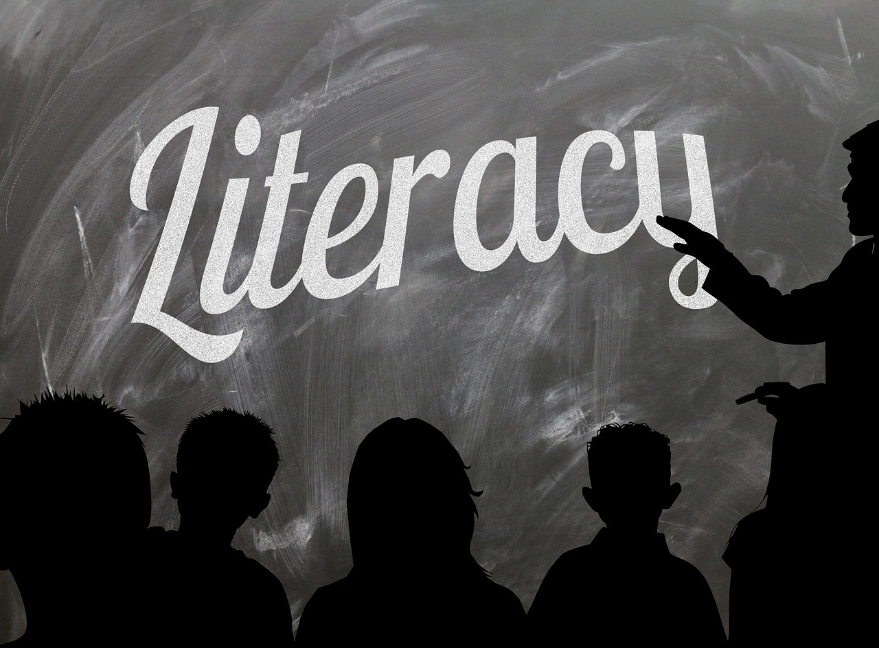 person in front of class with 'literacy' on chalk board