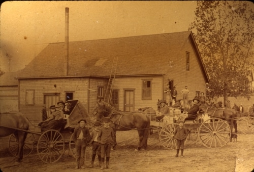 People and horse-drawn buggies in front of building