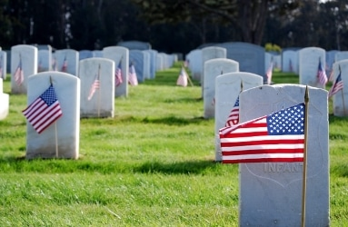 military graveyard with american flags by headstones